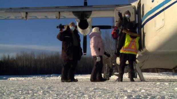 The vaccination team waves goodbye as they board their flight from Nahanni Butte after finishing their vaccination clinic.