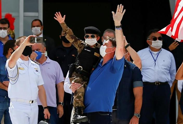 Brazil's President Jair Bolsonaro, pictured (center, in blue) on May 17, shares his US counterpart's tendency to disregard scientific evidence that contradicts him (AFP Photo/Sergio LIMA)