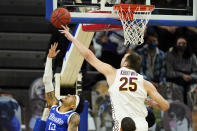 Loyola of Chicago center Cameron Krutwig (25) blocks a shot by Drake guard Roman Penn, left, during the first half of an NCAA college basketball game, Sunday, Feb. 14, 2021, in Des Moines, Iowa. (AP Photo/Charlie Neibergall)