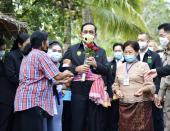 In this photo released by Government Spokesman Office, Thailand's Prime Minister Prayuth Chan-ocha receives flowers from well wishers in Samut Songkhram province, Thailand, Wednesday, Dec. 2, 2020. Thailand's highest court is set to rule Wednesday, Dec. 2, on whether Prayuth has breached ethics clauses in the country's constitution and should be ousted from his position. (Government Spokesman Office via AP)