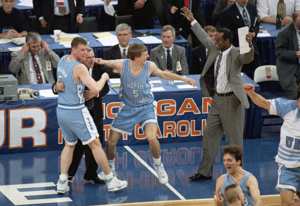 FILE - In this April 5, 1993, file photo, North Carolina coach Dean Smith is hugged by Pat Sullivan, left, as Henrik Rodl (5) and assistant coach Randy Weil, right, celebrate the team's 77-71 win over Michigan for the NCAA men's basketball championship in New Orleans. Rodl, now the coach of the German team, says it's an honor to coach in the Olympics, just as Smith did in 1976. (AP Photo/Bill Haber, File)