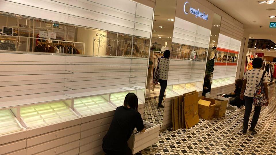 Staff removing goods off the shelves and packing them into boxes at The Heeren outlet. Photo: Coconuts