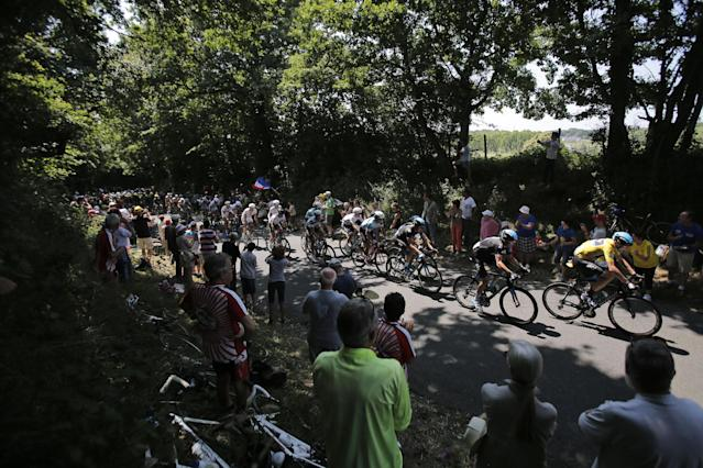 The pack with Christopher Froome of Britain, wearing the overall leader's yellow jersey, passes during the twelfth stage of the Tour de France cycling race over 218 kilometers (136.2 miles) with start in in Fougeres and finish in Tours, western France, Thursday July 11 2013. (AP Photo/Christophe Ena)