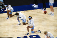 North Carolina players kneel during the national anthem before a college basketball game against Alabama in the first round of the women's NCAA tournament at the Alamodome in San Antonio, Monday, March 22, 2021. (AP Photo/Eric Gay)