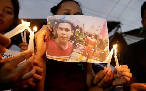 <span>Activists light candles in front of the picture of 17-year-old student Kian Loyd delos Santos in Manila</span> <span>Credit: AP Photo/Aaron Favila </span>