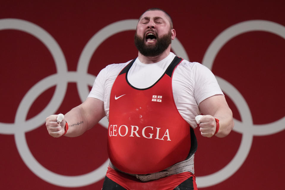 Lasha Talakhadze of Georgia celebrates after winning gold in the men's +109kg weightlifting event, at the 2020 Summer Olympics, Wednesday, Aug. 4, 2021, in Tokyo, Japan. (AP Photo/Luca Bruno)
