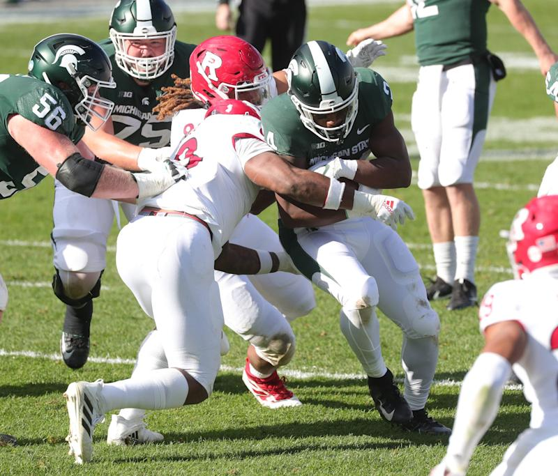 Michigan State running back Elijah Collins is tackled by Rutgers linebacker Tyshon Fogg during MSU's 38-27 loss on Saturday, Oct. 24, 2020, at Spartan Stadium.