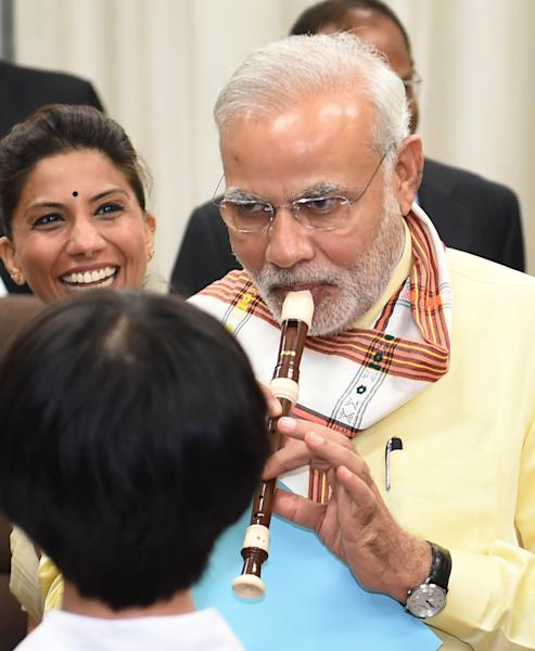 Indian Prime Minister Narendra Modi (R) plays a recorder as he visits a music class at an elementary school in Tokyo, on September 1, 2014 (AFP Photo/Kazuhiro Nogi)