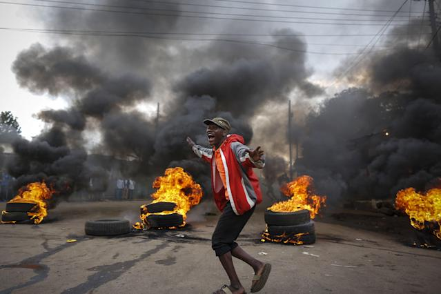<p>A supporter of the opposition coalition the National Super Alliance (NASA) and its presidential candidate Raila Odinga reacts in front of a burning barricade he and others set up to block vehicles from delivering electoral materials to the polling stations in ther areas in Kibera slum, one of the opposition strongholds in Nairobi, Kenya, Oct. 25, 2017, a day before the scheduled repeat presidential poll. (Photo: Dai Kurokawa/EPA-EFE/REX/Shutterstock) </p>