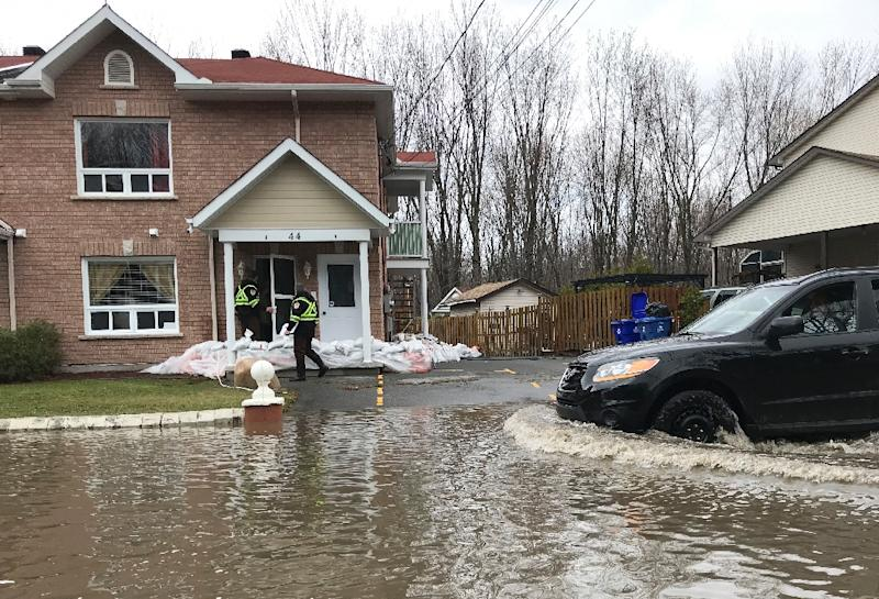 Firefighters check on people in their homes in preparation for increased flooding in Gatineau, Quebec (AFP Photo/Michel COMTE)
