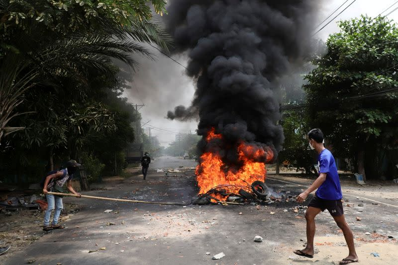 An anti-coup protester walks past burning tires, in Yangon
