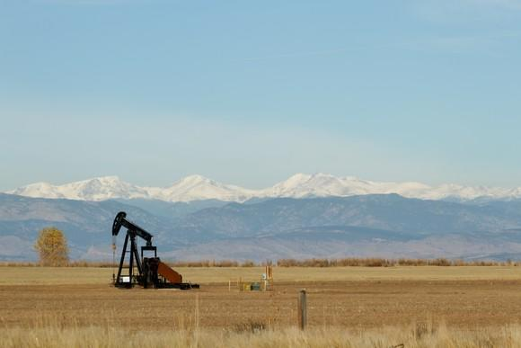 An oil pump in the field with mountains in the background.