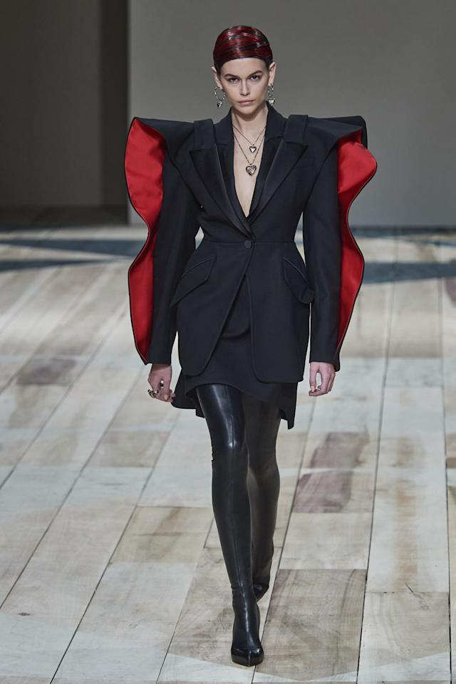 """<p>Sarah Bruton said she wanted this collection to be """"really grounded, bold, and heroic,"""" and I think that is exactly what we all need right now. Kaia Gerber embodies the modern McQueen warrior woman with her graphic tailored jacket and skinny legging pant in black (the color of the season), accented with the Welsh bold red, which signifies protection, healing, and strength—three things we are all craving in this uncertain time. —<em>Joanna Hillman, Style Director</em></p>"""