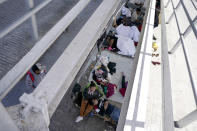 FILE - In this Thursday, March 18, 2021, file photo migrants who were caught trying to sneak into the United States and deported rest under a ramp that leads to the McAllen-Hidalgo International Bridge point of entry into the U.S. in Reynosa, Mexico. A surge of migrants on the Southwest border has the Biden administration on the defensive. The head of Homeland Security acknowledged the severity of the problem Tuesday but insisted it's under control and said he won't revive a Trump-era practice of immediately expelling teens and children. (AP Photo/Julio Cortez)