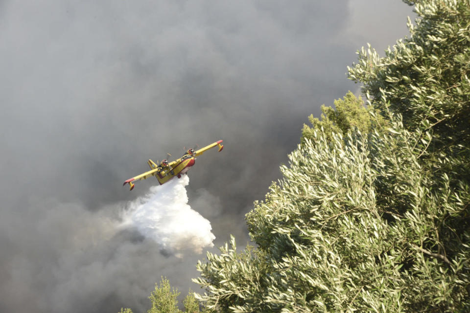 An airplane drops water over a wildfire near Lampiri village, west of Patras, Greece, Saturday, Jul. 31, 2021. The fire, which started high up on a mountain slope, has moved dangerously close to seaside towns and the Fire Service has send a boat to help in a possible evacuation of people. (AP Photo/Andreas Alexopoulos)