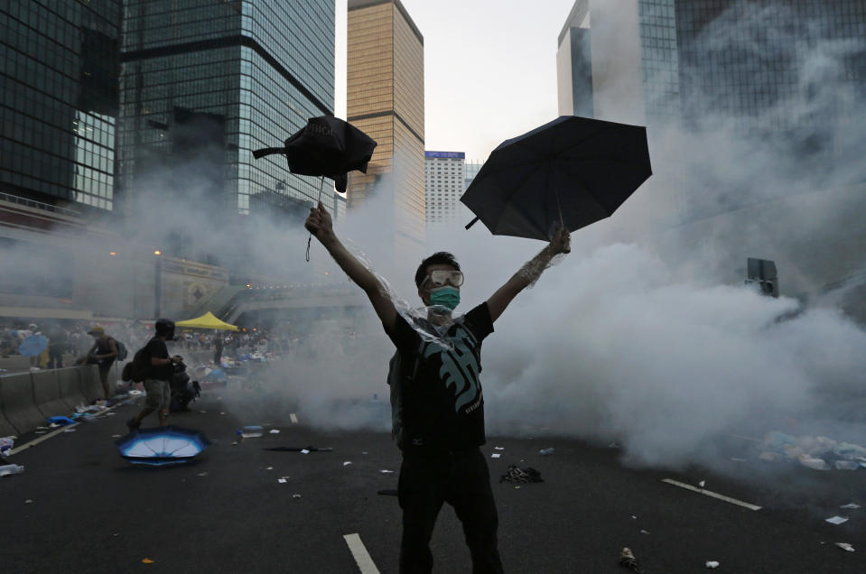 A protester (C) raises his umbrellas in front of tear gas which was fired by riot police to disperse protesters blocking the main street to the financial Central district outside the government headquarters in Hong Kong, September 28, 2014. Hong Kong police used tear gas for the first time on Sunday to disperse pro-democracy protests and baton-charged the crowd blocking a key road in the government district after Hong Kong and Chinese officials warned against illegal demonstrations. REUTERS/Tyrone Siu (CHINA - Tags: CIVIL UNREST POLITICS TPX IMAGES OF THE DAY)