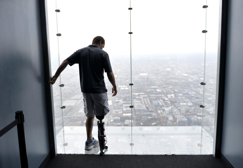 """Zac Vawter, fitted with an experimental """"bionic"""" leg, looks out onto the Ledge at the Willis Tower, Thursday, Oct. 25, 2012 in Chicago. Vawter is training for the world's tallest stair-climbing event where he'll attempt to climb 103 flights to the top of the Willis Tower using the new prosthesis.  Vawter will put his bionic leg to the ultimate test Sunday, Nov. 4,  when he attempts to climb 103 flights of stairs to the top of Chicago's Willis Tower, one of the world's tallest skyscrapers. If all goes well, he'll make history with the bionic leg's public debut.  (AP Photo/Brian Kersey)"""