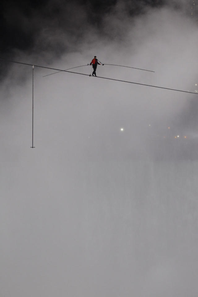 Nik Wallenda walks across Niagara Falls on a wire in Niagara Falls, N.Y., Friday, June 15, 2012. Wallenda has finished his attempt to become the first person to walk on a tightrope 1,800 feet across the mist-fogged brink of roaring Niagara Falls. The seventh-generation member of the famed Flying Wallendas had long dreamed of pulling off the stunt, never before attempted. (AP Photo/David Duprey)