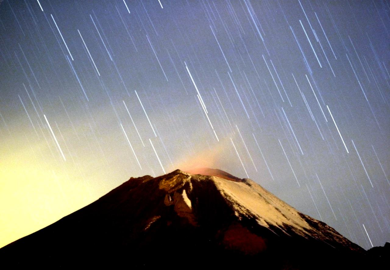 A meteor shower lights up the sky over the Mexican volcano Popocatepetl near the village San Nicolas de los Ranchos in Mexican state of Puebla in the early hours of December 14, 2004. The shower, named Geminid because it appears to originate from the constellation Gemini, lit up the sky with dozens of shooting stars per hour. REUTERS/Daniel Aguilar