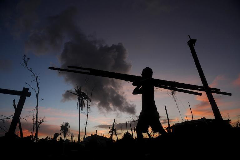 A man collects wood to construct a house in Palo, Leyte province, central Philippines, in November 24, 2013