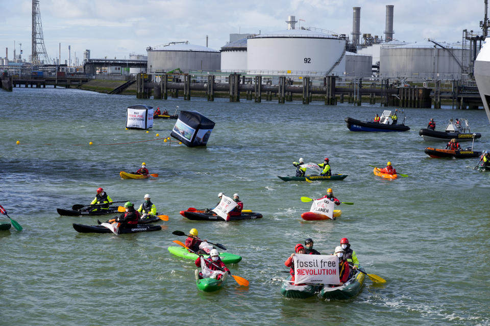 Greenpeace climate activists paddle ashore after Dutch police broke up a protest at a Shell refinery in Rotterdam, Netherlands, Monday, Oct. 4, 2021. A coalition of environmental groups launched a campaign calling for a Europe-wide ban on fossil fuel advertising ahead of the United Nations Climate Change Conference, also known as COP26, which start in Glasgow on Oct. 31st, 2021. (AP Photo/Peter Dejong)