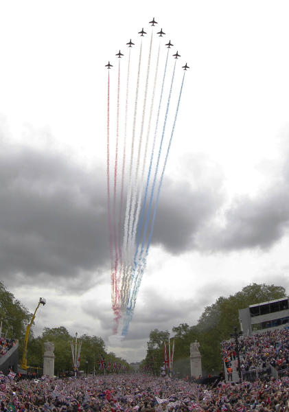 Royal Air force Red Arrow display team fly pass Buckingham Palace in London where Britain Queen Elizabeth II watches from the palace balcony as part of a four-day Diamond Jubilee celebration to mark the 60th anniversary of Queen Elizabeth II accession to the throne, Tuesday, June 5, 2012. (AP Photo/Sang Tan)