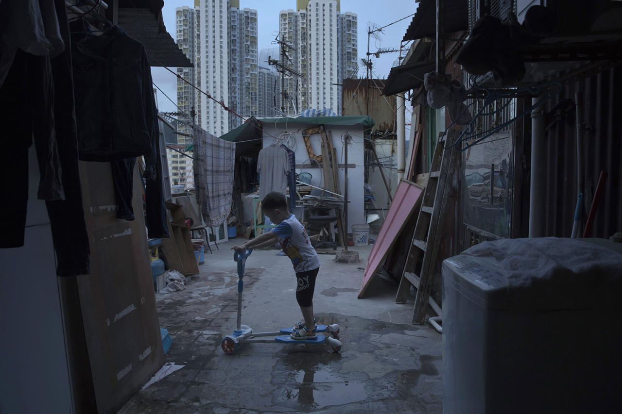 <p>A five-year-old boy plays outside his tiny home, which is made of concrete and corrugated metal, on the terrace of an apartment block in Hong Kong, April 20, 2017. He lives with his parents in an illegal rooftop hut located next to a public housing estate. (Photo: Kin Cheung/AP) </p>