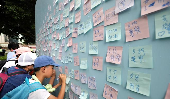 Rally attendees sign Post-it notes on a pro-establishment Lennon Wall. Photo: Felix Wong