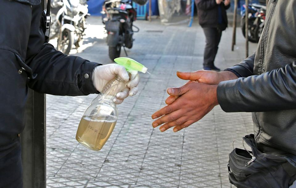 An Iranian man sprays alcohol on the hands of people outside an office building in Tehran on March 4. Source: Getty Images