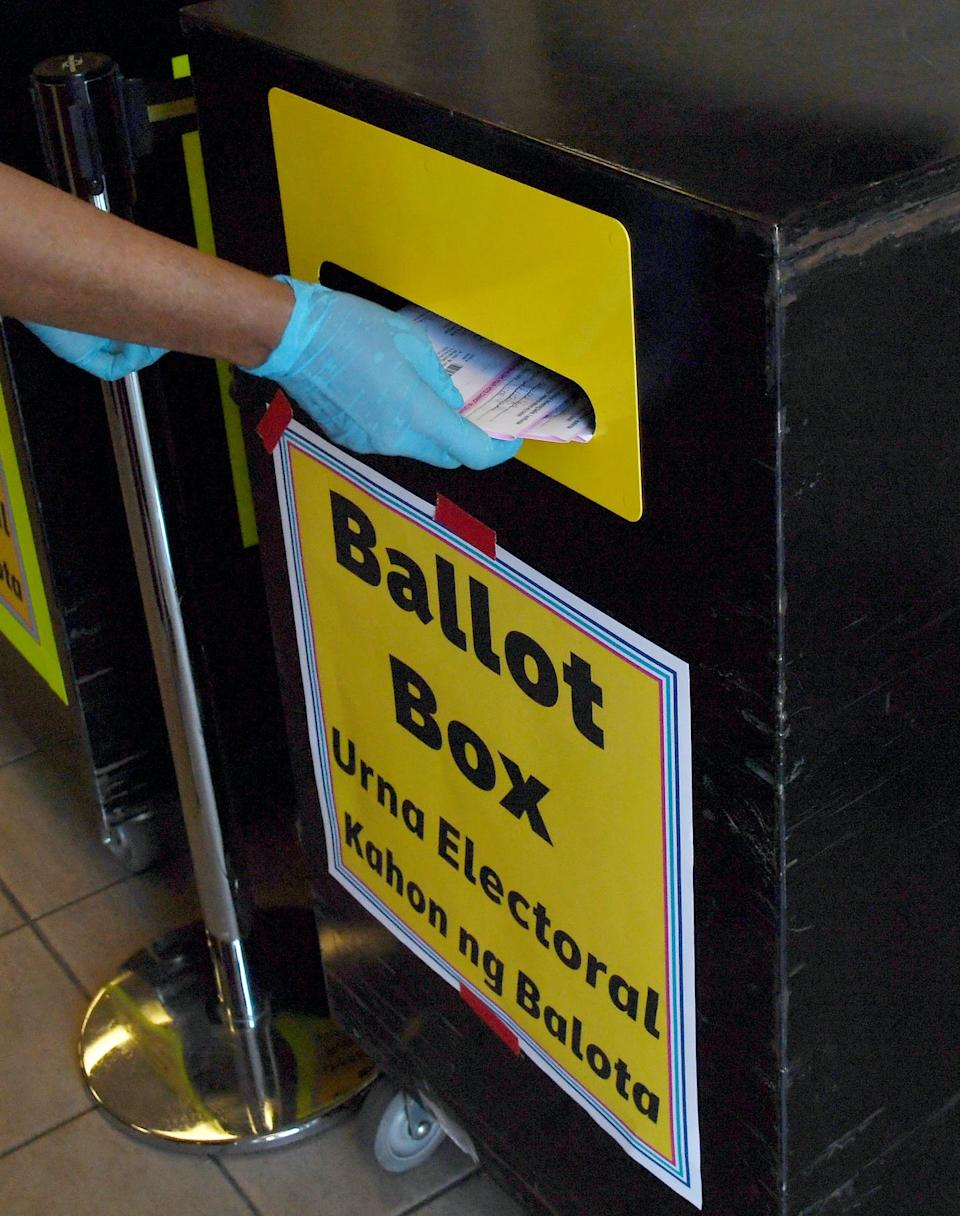An election worker puts mail-in ballots collected from vehicles in a ballot box