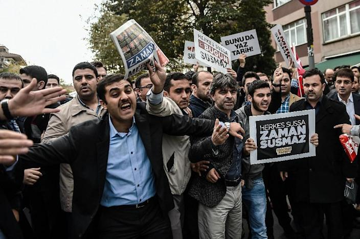 """Supporters of Bugun and Kanalturk media groups shout slogans towards Turkish riot police and hold signs reading """"Bugun is not alone-if everybody is silent, Bugun won't be"""" on October 27, 2015 in Istanbul (AFP Photo/Ozan Kose)"""