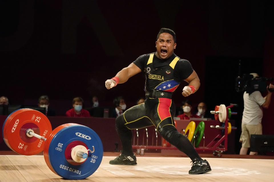 Keydomar Giovan Vallenilla Sanchez of Venezuela celebrates after the last lift in the men's 81kg weightlifting event, at the 2020 Summer Olympics, Saturday, July 31, 2021, in Tokyo, Japan. (AP Photo/Luca Bruno)