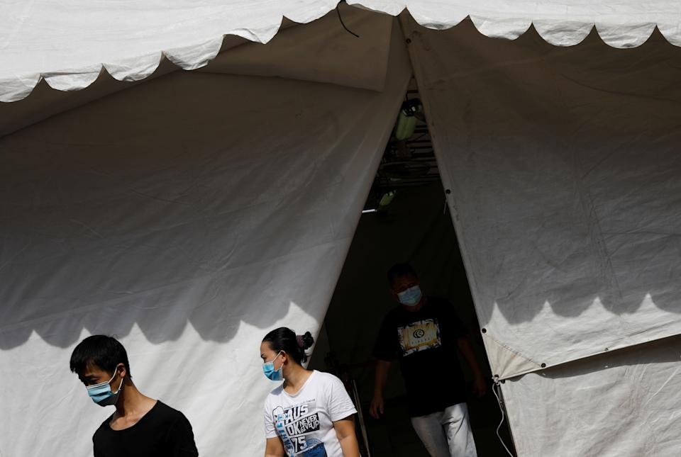 People leave a tent used as a thermal scanning station, while buying groceries, amid the outbreak here on 23 April. 2020. (PHOTO: Reuters)