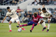 Dallas FC forward Jader Obrian, center, is defended by Los Angeles FC midfielder Eduard Atuesta, left, and defender Eddie Segura during the first half of an MLS soccer match Wednesday, June 23, 2021, in Los Angeles. (AP Photo/Marcio Jose Sanchez)