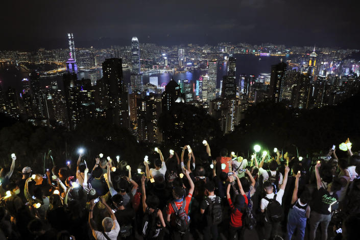 FILE - In this Friday, Sept. 13, 2019 file photo, demonstrators hold up the mobile phone lights as they form a human chain at the Peak, a tourist spot in Hong Kong. Hong Kong has a long tradition of public demonstrations dating from its days as a British colony. However, protest activity has been tamped down since Beijing enacted a sweeping security law in June 2020, banning speech seen as promoting secession. (AP Photo/Kin Cheung)
