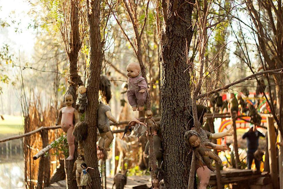 """<p>This haunted location is not for the faint of heart. Isla de las Munecas in Mexico, aka Island of the Dolls, was never intended to be a tourist destination. Legend says a girl was found mysteriously drowned on the island by its caretaker Don Julian Santana Barrera. He found a doll nearby and assuming it was hers, he hung it to a tree as a way of showing respect. He was apparently haunted by the spirit of the girl after that and started hanging more dolls in an attempt to please her. People say the dolls are now possessed by her spirit. Some even claim they hear the dolls whispering to each other, according to the <a href=""""https://isladelasmunecas.com/"""" rel=""""nofollow noopener"""" target=""""_blank"""" data-ylk=""""slk:island's website"""" class=""""link rapid-noclick-resp"""">island's website</a>.</p>"""