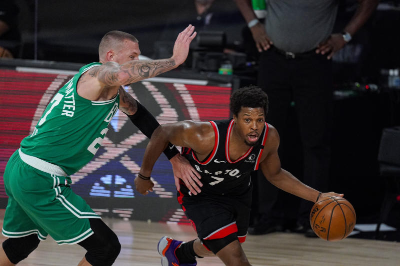 Toronto Raptors guard Kyle Lowry (7) dribble away from Boston Celtics center Daniel Theis (27) during the first half of an NBA conference semifinal playoff basketball game Wednesday, Sept. 9, 2020, in Lake Buena Vista, Fla. (AP Photo/Mark J. Terrill)