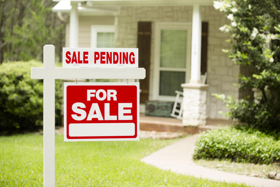 """Red and white """"Sale Pending, Home for Sale"""" sign in front of a stone, wood house that is for sale and has recently been sold. Green grass and bushes indicate the spring or summer season. Front porch and windows in background. Real estate signs in residential neighborhood.  Moving house, relocation concepts."""
