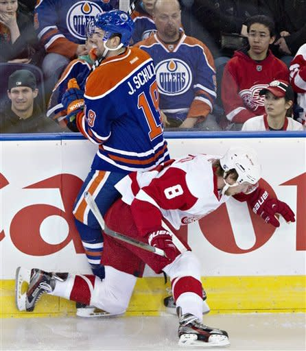 Detroit Red Wings' Justin Abdelkader (8) checks Edmonton Oilers' Justin Schultz (19) during the first period of an NHL hockey game Friday, March 15, 2013, in Edmonton, Alberta. (AP Photo/The Canadian Press, Jason Franson)