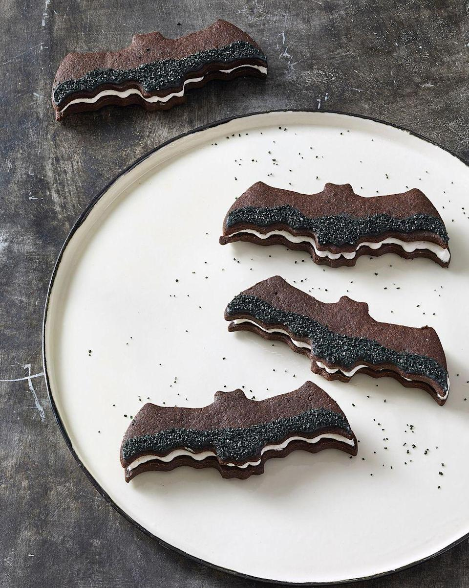 """<p>Add a little sparkle to the wings of these bat cookies with black sanding sugar. </p><p><em><a href=""""https://www.goodhousekeeping.com/food-recipes/party-ideas/a28609240/bat-sandwich-cookies-recipe/"""" rel=""""nofollow noopener"""" target=""""_blank"""" data-ylk=""""slk:Get the recipe for Bat Sandwich Cookies »"""" class=""""link rapid-noclick-resp"""">Get the recipe for Bat Sandwich Cookies »</a></em></p><p><strong><strong>RELATED: </strong></strong><a href=""""https://www.goodhousekeeping.com/holidays/halloween-ideas/g244/halloween-desserts/"""" rel=""""nofollow noopener"""" target=""""_blank"""" data-ylk=""""slk:Spooky Halloween Desserts and Treats You Need to Make this October"""" class=""""link rapid-noclick-resp"""">Spooky Halloween Desserts and Treats You Need to Make this October</a></p>"""