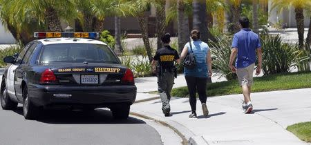 Orange County Sheriff deputy escorts a couple to their home on a street near a house where four people were found dead, in Mission Viejo