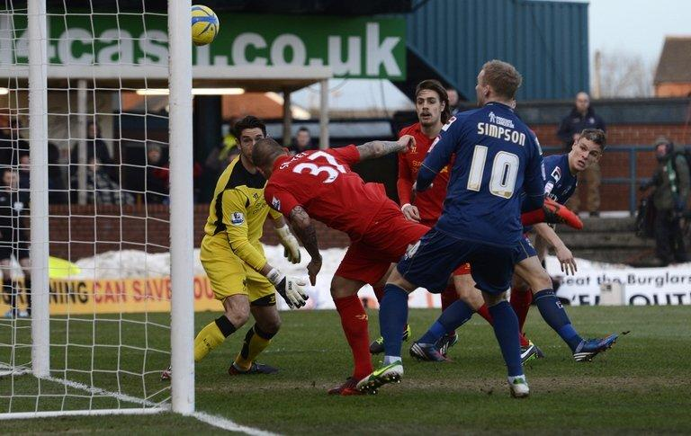 Oldham Athletic's Matt Smith (R) scores against Liverpool in the FA Cup fourth round at Boundary Park on January 27, 2013. Oldham, three-time semi-finallists, joined fellow third-tier side Milton Keynes Dons, Championship clubs Millwall and Leeds United, and non-league Luton Town in claiming a famous Premier League scalp