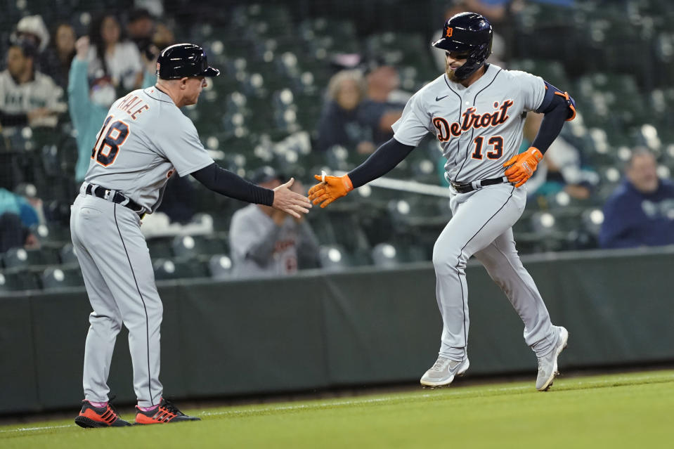 Detroit Tigers' Eric Haase (13) is greeted by third base coach Chip Hale after Haase hit a solo home run during the second inning of a baseball game against the Seattle Mariners, Monday, May 17, 2021, in Seattle. (AP Photo/Ted S. Warren)