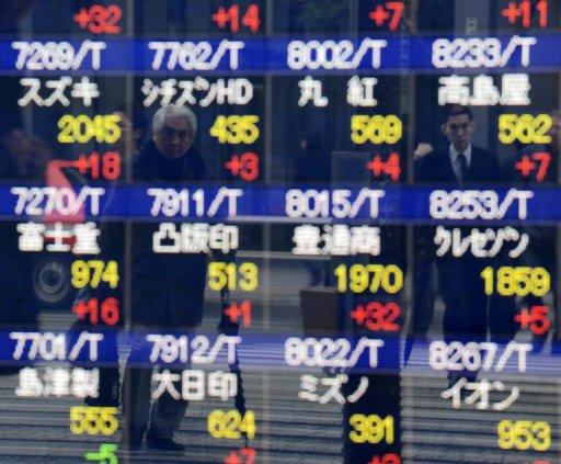 Pedestrians are reflected on a share prices board in Tokyo on December 17, 2012