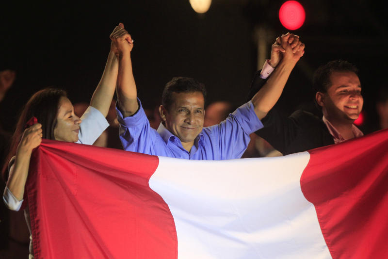 Peru's presidential candidate Ollanta Humala, center, raises hands with his running mates First Vice President Marisol Espinoza, left, and Second Vice President Omar Chehade after the presidential runoff election in Lima, Peru, Sunday June 5, 2011. Humala declared victory over rival candidate Keiko Fujimori in Peru's tightly contested presidential runoff, with official results incomplete but showing him winning. (AP Photo/Martin Mejia)