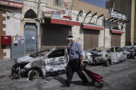 A man passes by cars torched after a night of violence between Israeli Arab protesters and Israeli police in the mixed Arab-Jewish town of Lod, central Israel, Tuesday, May 11, 2021. (AP Photo/Heidi Levine)