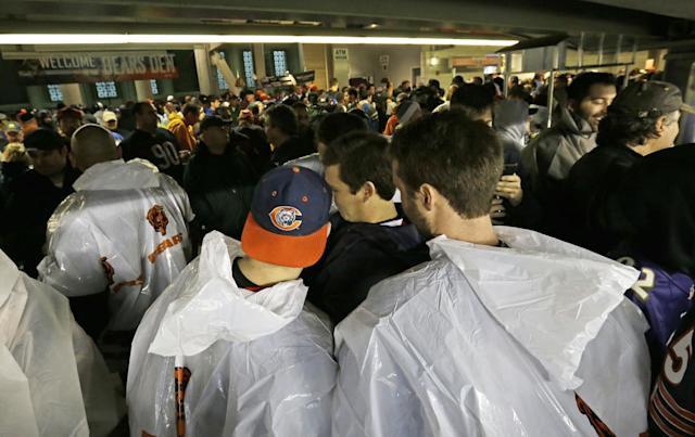 Fans seek shelter in the concourse area at Soldier Field as a severe storm blows through the area during the first half of an NFL football game between the Chicago Bears and Baltimore Ravens, Sunday, Nov. 17, 2013, in Chicago. Play was suspended in the game. (AP Photo/Nam Y. Huh)