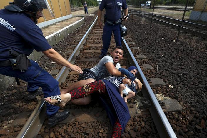 <p>Hungarian policemen stand over a family of refugees who threw themselves onto the track before they were detained at a railway station in the town of Bicske, Hungary, Sept. 3, 2015. <i>(Laszlo Balogh/Reuters)</i></p>