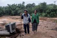 Ho Van Kang stands with his wife Ho Thi Nhe on ruins of their former house which was damaged by a landslide in Quang Tri province
