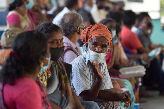 A migrant worker from Tamil Nadu waits to be screened along with other workers before travelling in a special train to his home state, at Ambedkar Stadium, on May 16, 2020 in New Delhi.